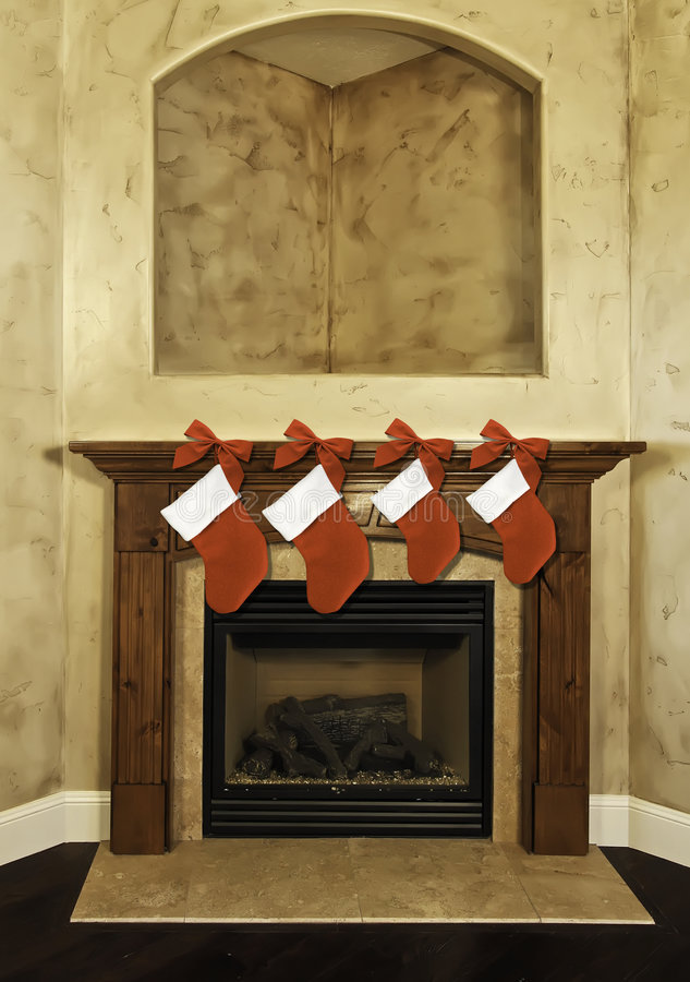 Christmas stockings on mantel. Four red Christmas stockings and red bows hanging along fireplace mantel royalty free stock photo