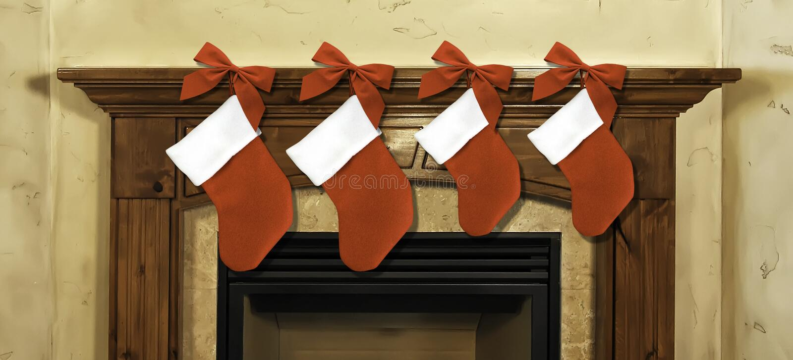 Christmas stockings on mantel. Four red Christmas stockings and red bow hanging along fireplace mantel royalty free stock photos