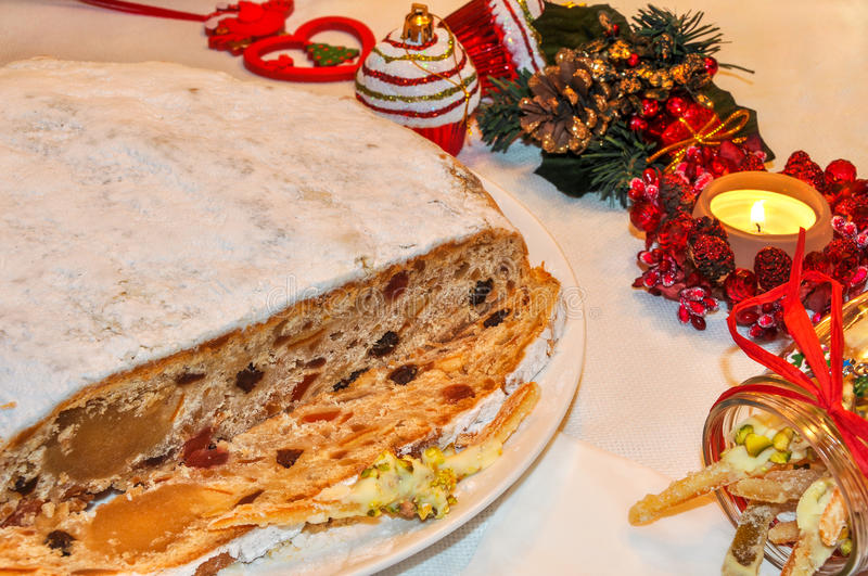 Christmas stollen, candied fruit, candle and decorations. royalty free stock photo
