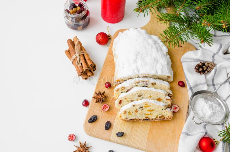Christmas stollen with mix dried fruits, nuts and icing sugar on the board. Traditional German Christmas Fruit Cake. Copy space. Horizontal orientation stock image