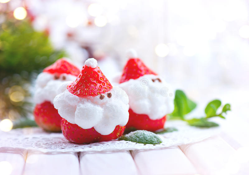 Christmas strawberry Santa. Funny dessert stuffed with whipped cream royalty free stock photos