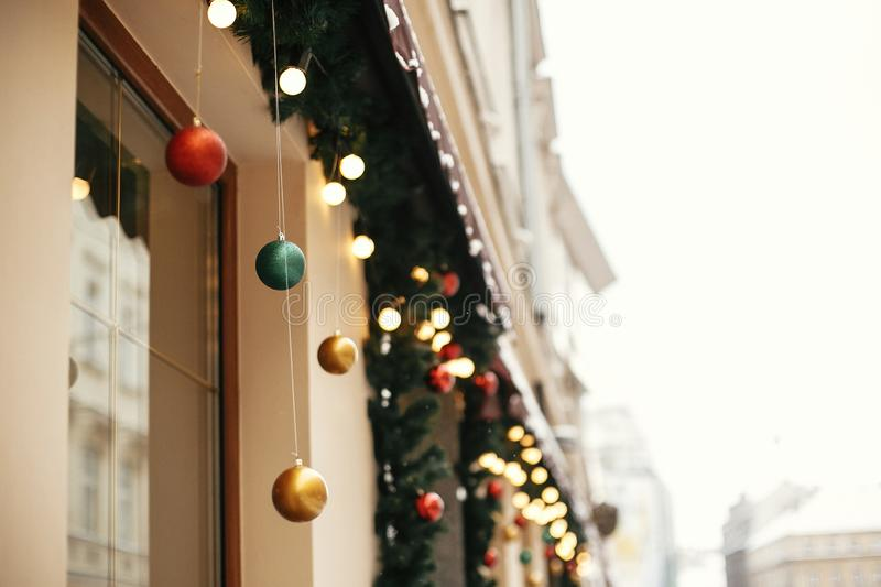 Christmas street decor. Stylish christmas fir branches with golden lights and colorful festive baubles in store window at holiday. Market in city street. Space royalty free stock photos