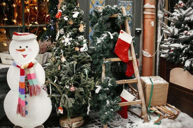 Christmas street decor. Stylish christmas tree with festive ornaments, snowman and ladder with stockings at store at holiday royalty free stock photo