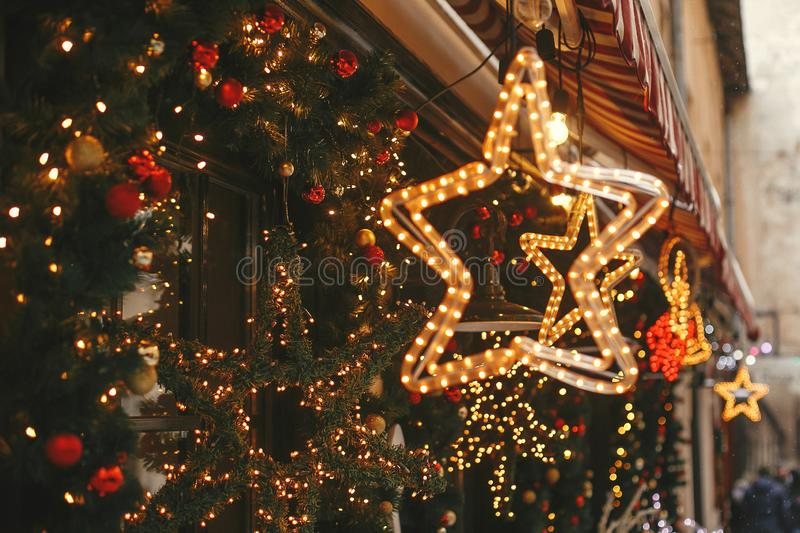 Christmas street decor. Stylish christmas golden star illumination and fir branches with red and gold baubles, golden lights bokeh. On front of building at royalty free stock photography
