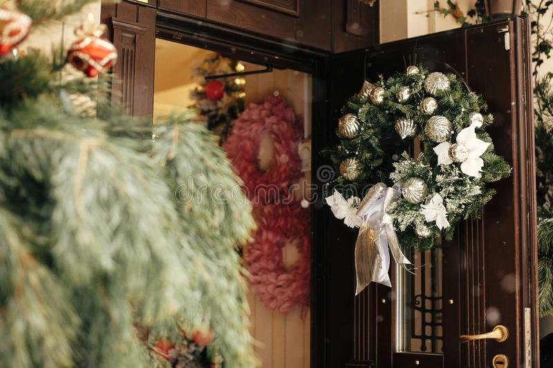 Christmas street decor. Stylish christmas wreath with silver ornaments on door at front store at holiday market in city street. Space for text. Rustic royalty free stock image