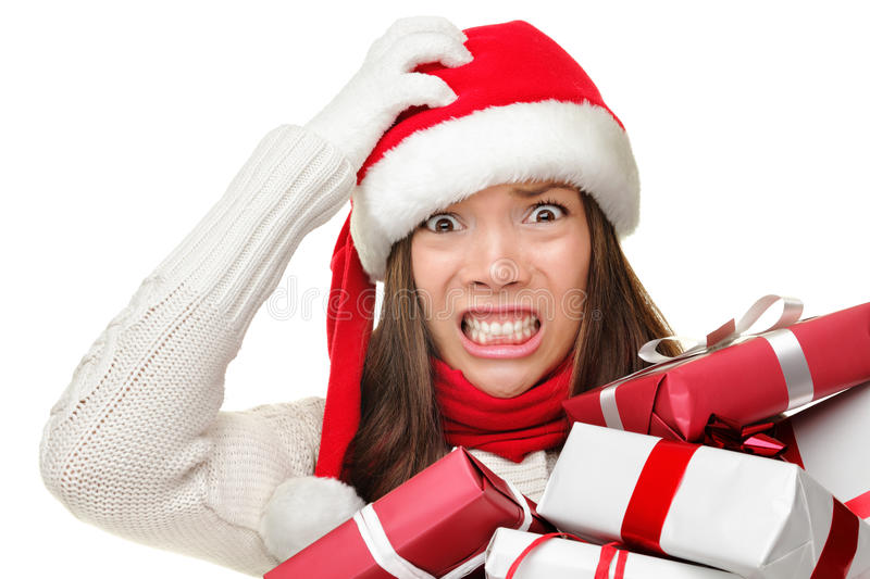 Christmas stress - busy santa woman. Christmas stress - busy woman wearing santa hat stressing for christmas shopping holding may christmas gifts in her arms stock image