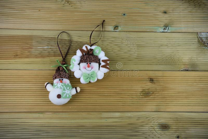 Christmas photography image with cute happy white soft material snowman decorations in green snowflake pattern scarf and hat stock image