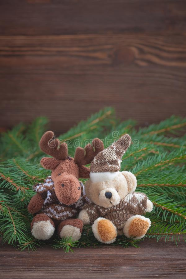 Christmas stuffed toys-a deer and a bear, Christmas-tree braches. Christmas stuffed toys - a deera nd a bear - near Christmas-tree braches on the wooden stock image
