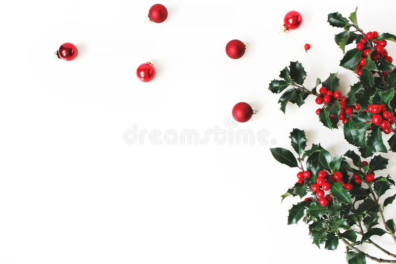 Christmas styled composition, decorative corner. Christmas glass balls, baubles and holly tree dark green leaves, red stock images