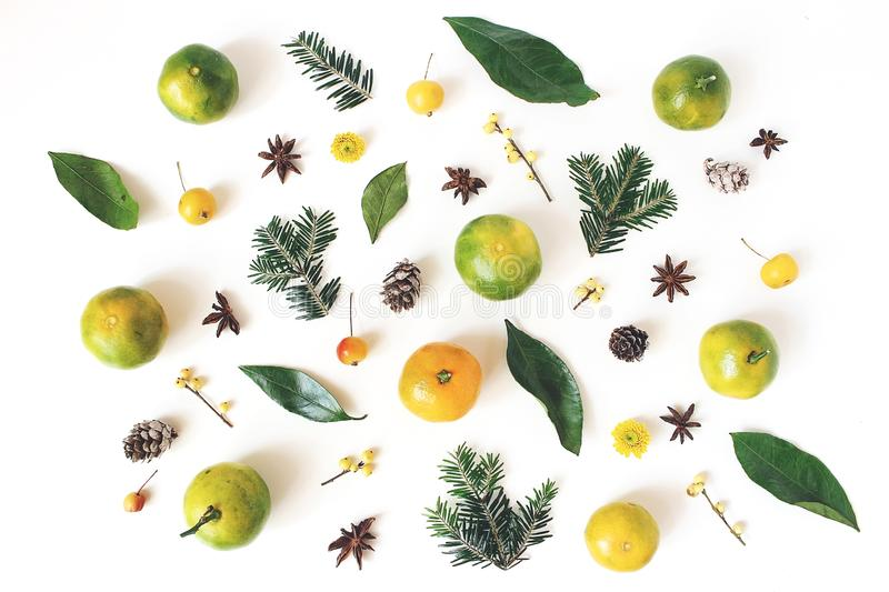 Christmas styled composition. Tangerine citrus fruit and leaves, fir tree branches, anise stars, holly berries and stock photo
