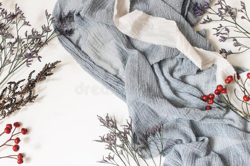 Christmas styled image composition. Winter weddding concept. Dusty blue muslin cotton fabric, silk ribbon, limon flowers stock photo