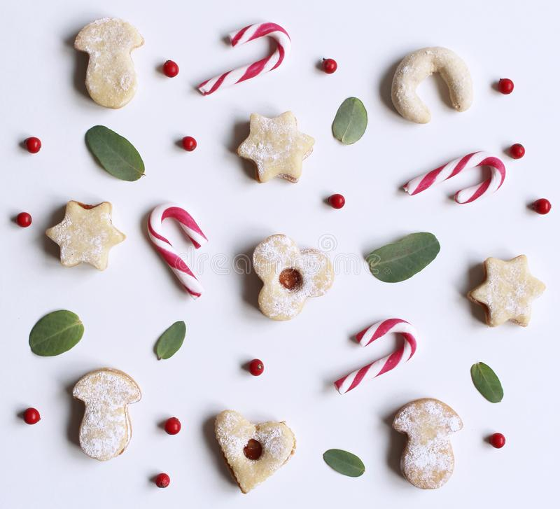 Christmas styled stock composition. Candy cane,homemade festive sweets and Eucalyptus leaves on white background. Flat stock images