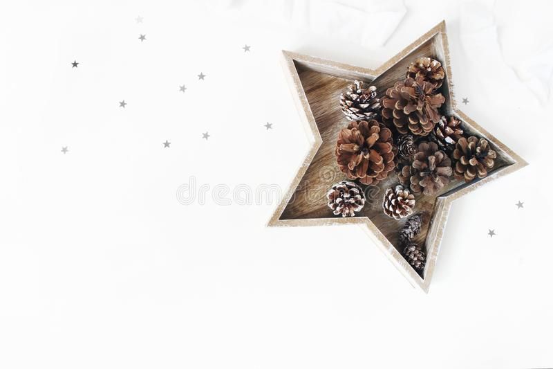 Christmas styled table composition. Pine and larch cones in star shaped wooden tray, silver confetti and silk ribbon royalty free stock images