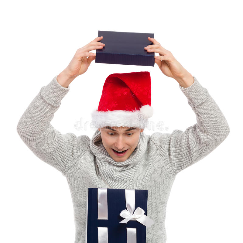 Christmas surprise. Surprised young man in santa's hat opening a gift. Studio portrait isolated on white royalty free stock photo