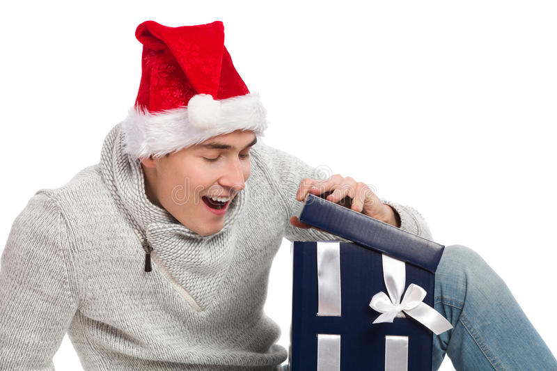 Christmas surprise. Young man in santas hat opening a gift. Studio portrait isolated on white royalty free stock image