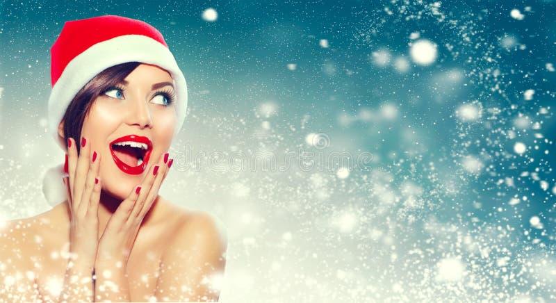Christmas. Surprised woman in Santa`s hat stock photo