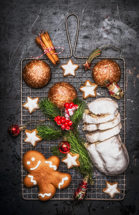 Christmas sweet baking food : homemade gingerbread, cookies, stollen with spices , fir branches and red holiday decoration on dark royalty free stock images