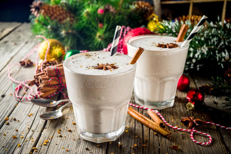 Christmas sweet cold drink, Homemade eggnog. Milkshake in two glasses with cinnamon and anise, old wooden background with xmas decorations copy space royalty free stock images