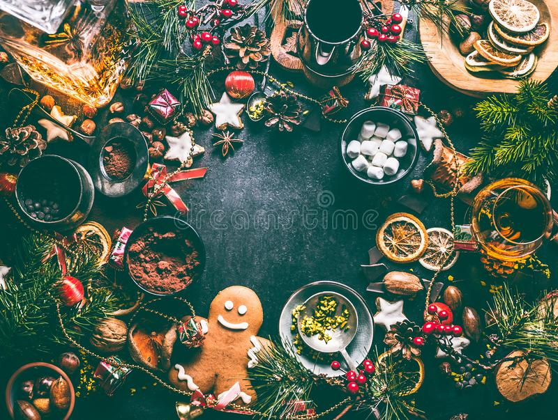 Christmas sweet food background with ingredients: nuts, dried fruits, spices, broken chocolate, cookies, gingerbread. Cacao, marshmallow and gingerbread man stock photography