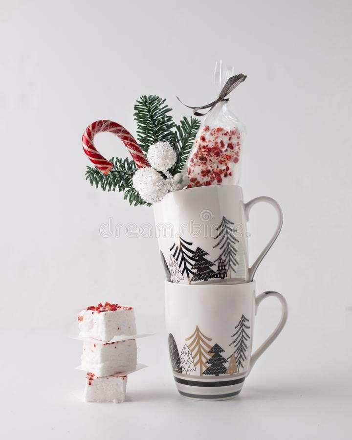 A Christmas sweet gift composition with fir, marshmellow, sweets in a mug on white background. royalty free stock image