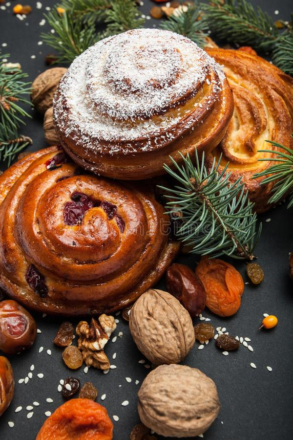 Christmas sweet homemade pastries, nuts, dried apricots, raisins and dates on a black background with a Christmas tree.  royalty free stock photography
