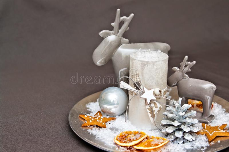 Christmas table decoration. Modern home Christmas table decoration with ceramic raindeer, candles, artificial snow and dry oranges slices on round plate with stock photography