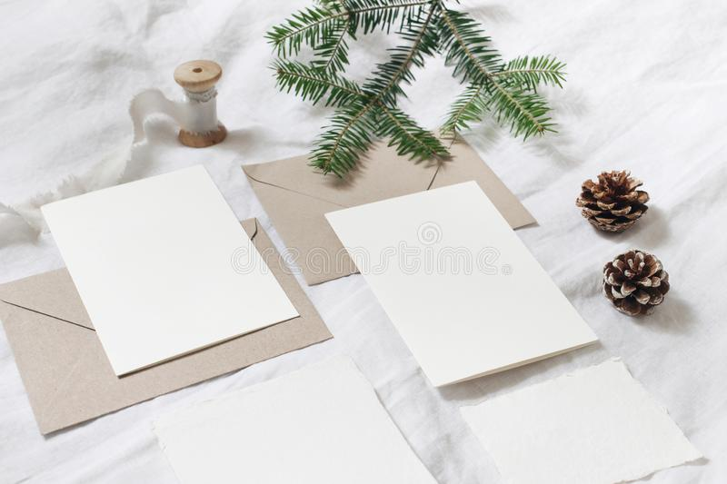 Christmas table, festive styled composition. Christmas greeting cards, envelopes mock-ups. Silk ribbon, pine cones and. Fir tree branch on white linen royalty free stock photography