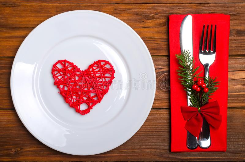 Christmas table: knife and fork, plate, napkin and Christmas tree branch on a wooden table top view with copy space. stock photography