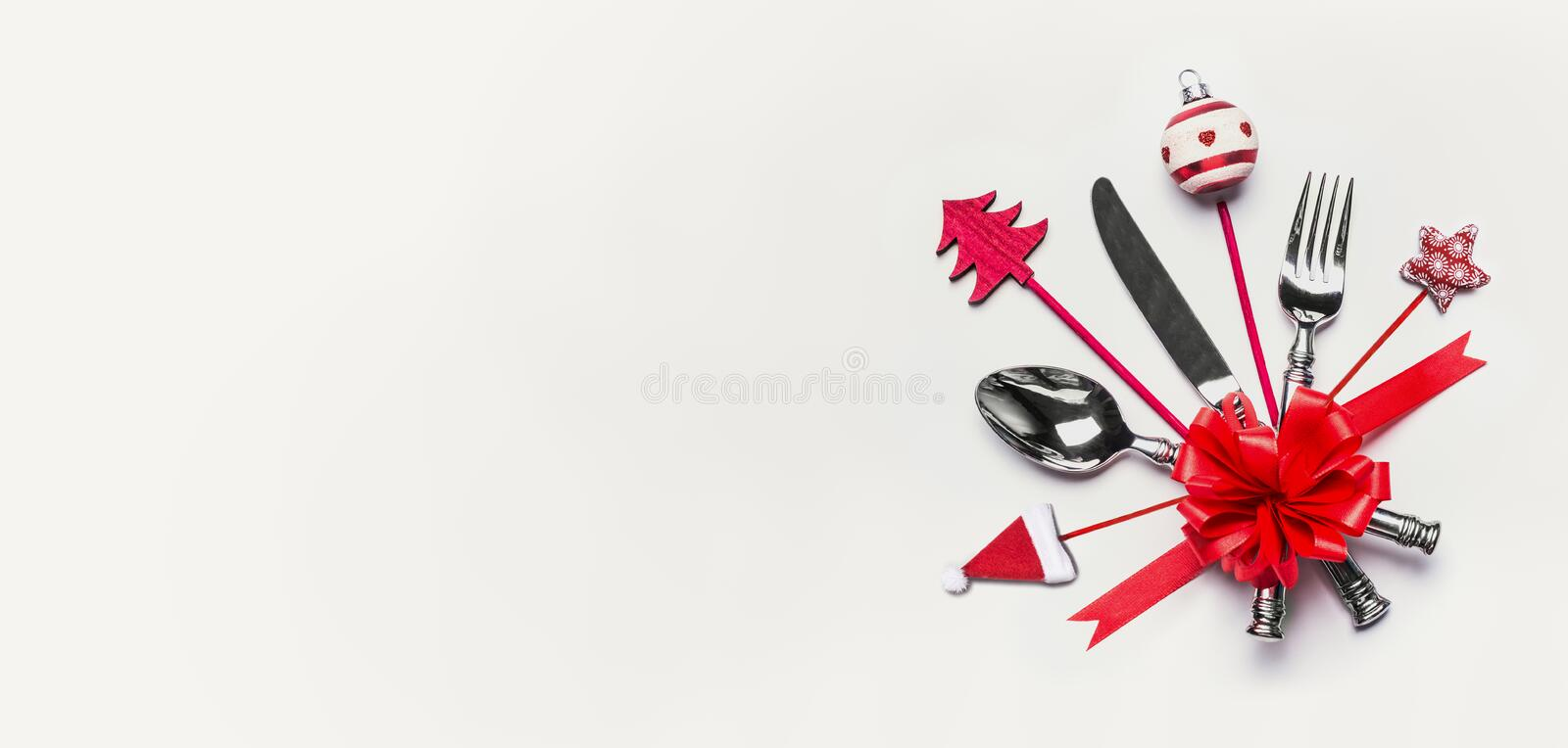 Christmas table place setting with cutlery, red ribbon and decoration with copy space on white desk background, top view, banner. royalty free stock images