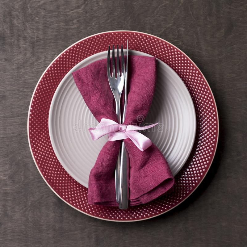 Christmas table place setting with empty gray and red plates with tableware at wood background stock photo
