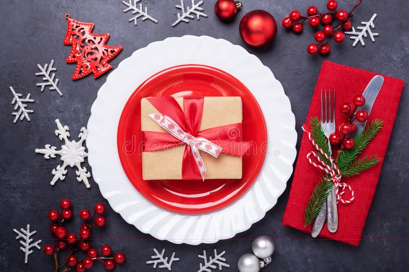 Christmas table place setting with empty red plate, cutlery with festive decorations star bow ball on stone background royalty free stock photography