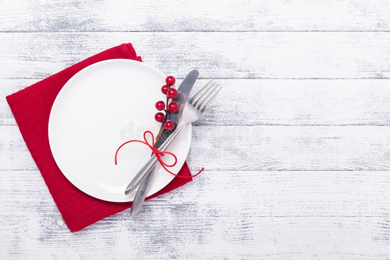 Christmas table place setting with empty white plate, cutlery with festive decorations on wooden background royalty free stock photo