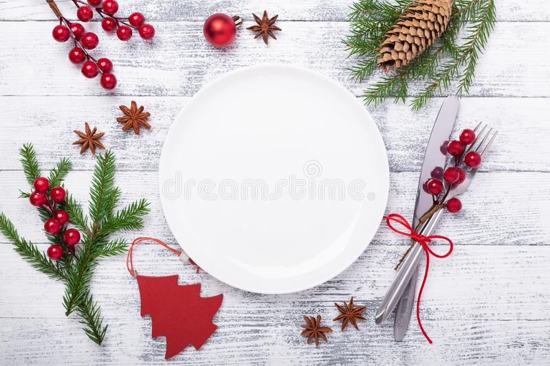 Christmas table place setting with empty white plate, cutlery with festive decorations on wooden background stock photo