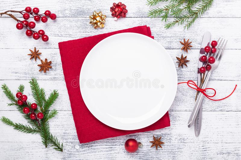 Christmas table place setting with empty white plate, cutlery with festive decorations on wooden background royalty free stock image