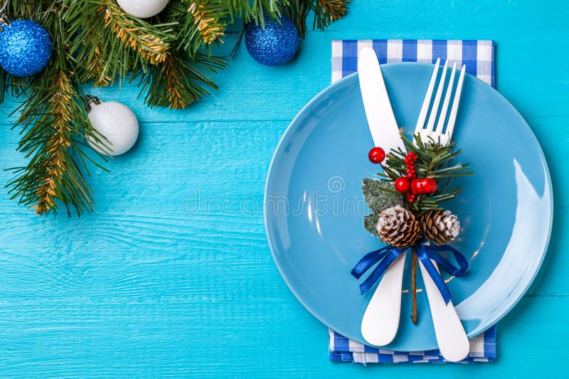 Christmas table place setting with napkin blue plate white fork and knife decorated sprig of mistletoe and christmas pine branches. & Christmas Table Place Setting With Napkin Blue Plate White Fork ...