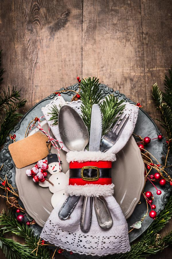 Christmas table place setting with plate, cutlery, fir branches , blank tag mock up and snowman on rustic wooden background royalty free stock image