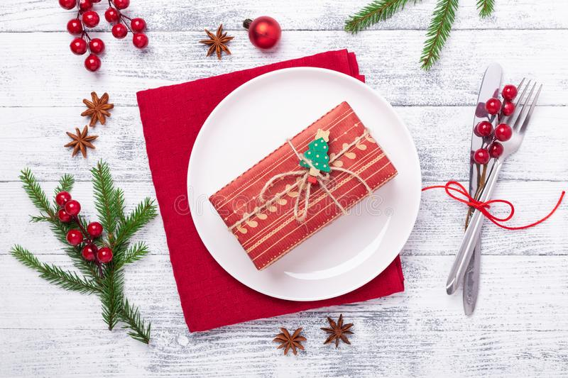 Christmas table place setting with white plate and gift box, cutlery with festive decorations on wooden background stock photography