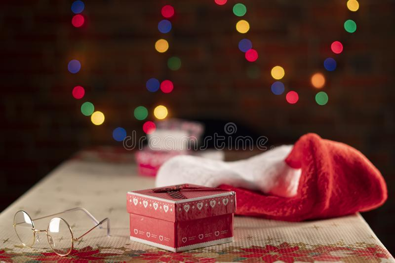 Christmas table with Santa Claus hat and glasses with gift boxes and colorful lights on a brick wall. Christmas Concept royalty free stock photography