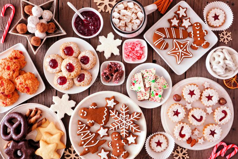 Christmas baking table scene with assorted sweets and cookies, top view over a rustic wood background. Christmas table scene of assorted sweets and cookies. Top stock photo