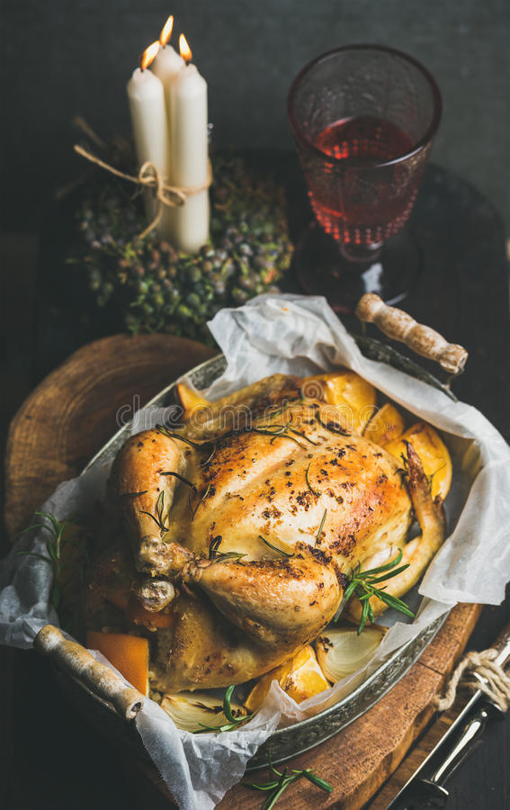 Christmas table set with oven roasted whole chicken and wine. Christmas holiday table set with roasted whole chicken stuffed with oranges, bulgur and rosemary stock photos