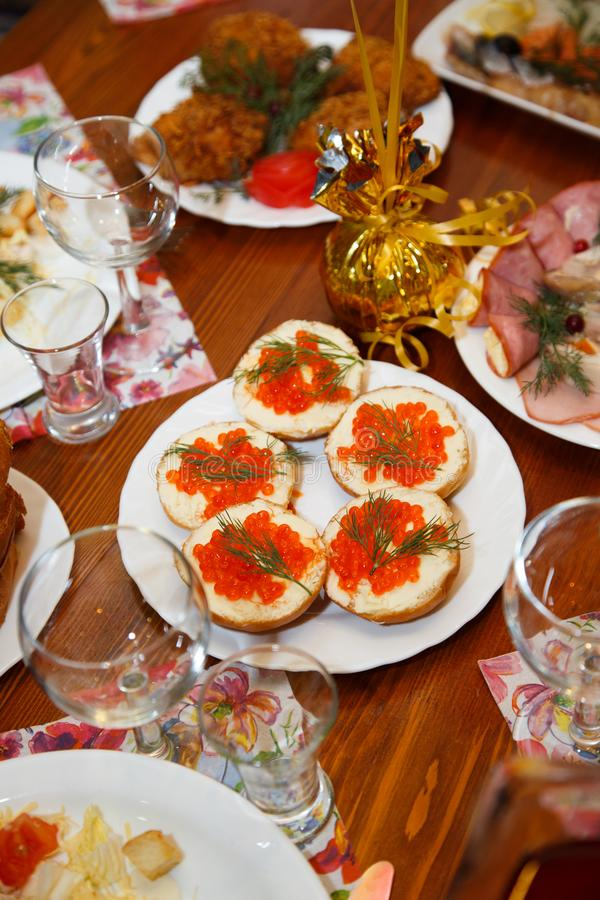 Christmas. Table set, side view. Sandwiches with red caviar. Meats on the holiday table. Table set, side view. Fried meat on a white porcelain plate. Holiday royalty free stock images