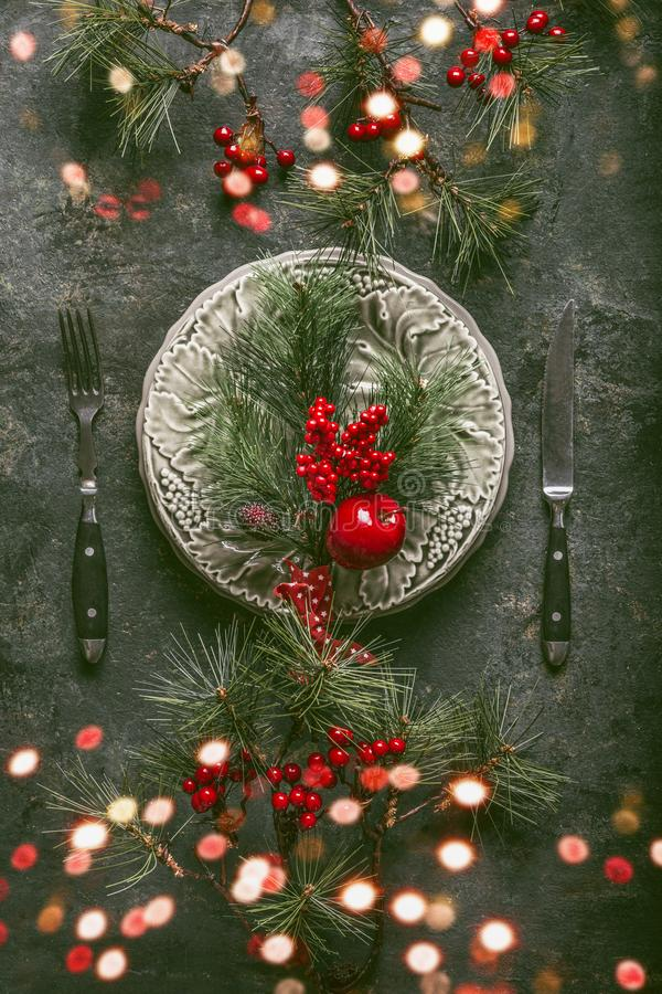 Christmas table setting with bokeh for holiday dinner with plate, cutlery, fir branches and winter berries on rustic background royalty free stock photo