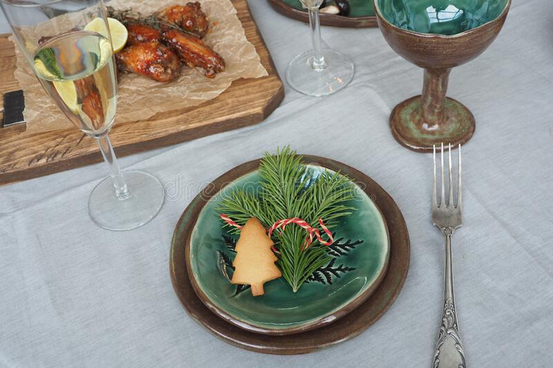 Christmas table setting. Brown-green vintage plates, vintage fork, spruce branch and gingerbread tree, fried meat on a wooden tray. Gray tablecloth and stars royalty free stock photography