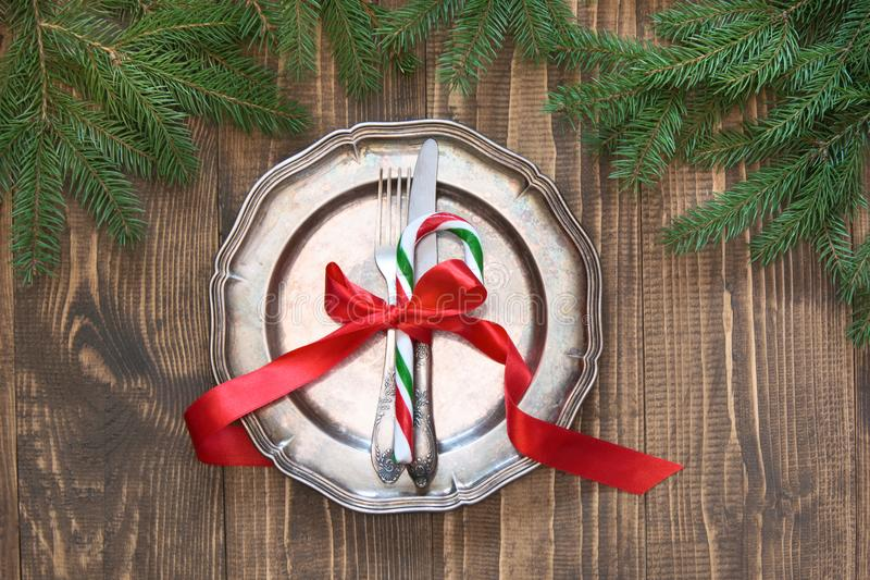 Christmas table setting with candy cane and red ribbon as decor, vintage dishware, silverware and decorations on board. Christmas table setting with candy cane stock images