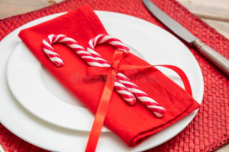 Candy canes on white plates and napkin, red background, closeup view stock photography