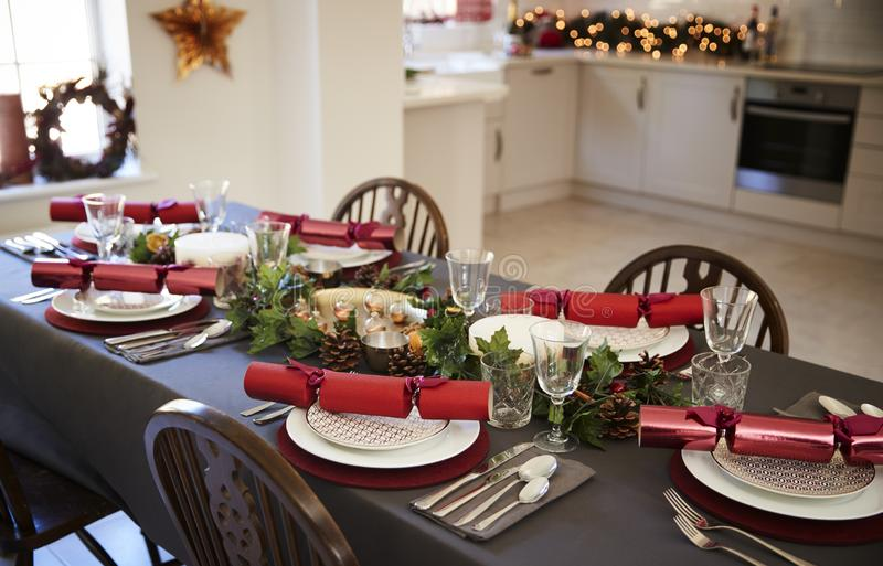 Christmas table setting with Christmas crackers arranged on plates in a dining room, with kitchen in the background stock image