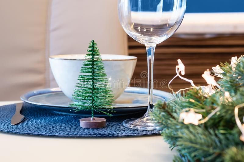 Christmas table setting with classic blue color accessories. Spruce wreath and stars garland, selective focus royalty free stock images