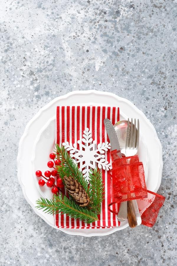 Christmas table setting with empty festive white plate and cutlery with Xmas decorations, snowflake, cone, Xmas tree branches stock images
