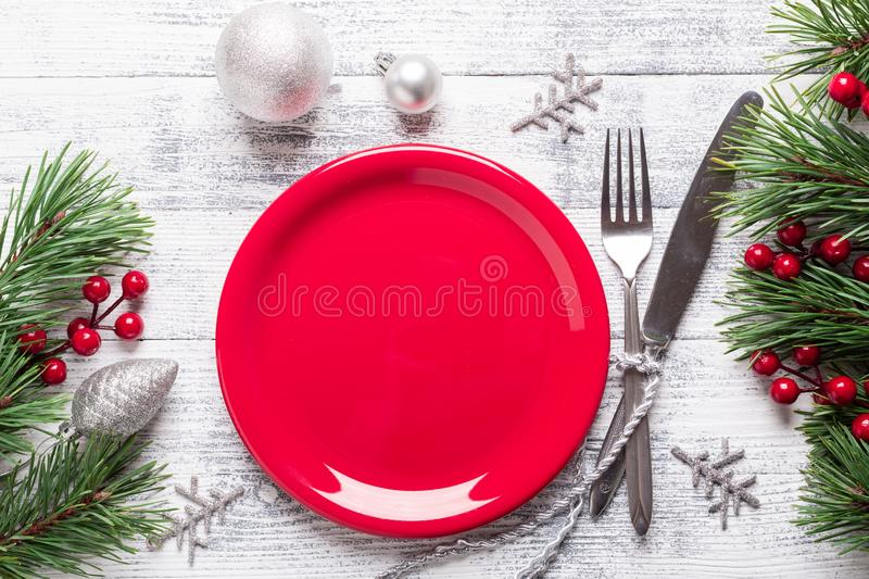 Christmas table setting with empty red plate, gift box and silverware on light wood background. Fir tree branch. royalty free stock photos
