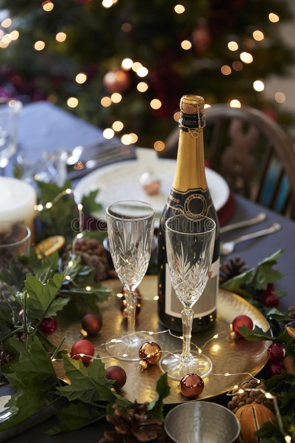 Christmas table setting with glasses and a bottle of champagne, baubles arranged on a gold plate and green and red table decoratio stock image